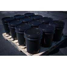 Pallet showing twelve buckets of 5 gallon BIGA asphalt sealer