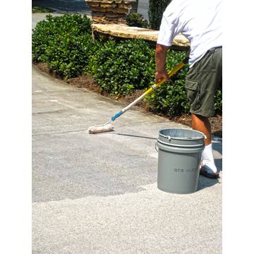image of a man applying clear driveway concrete sealer